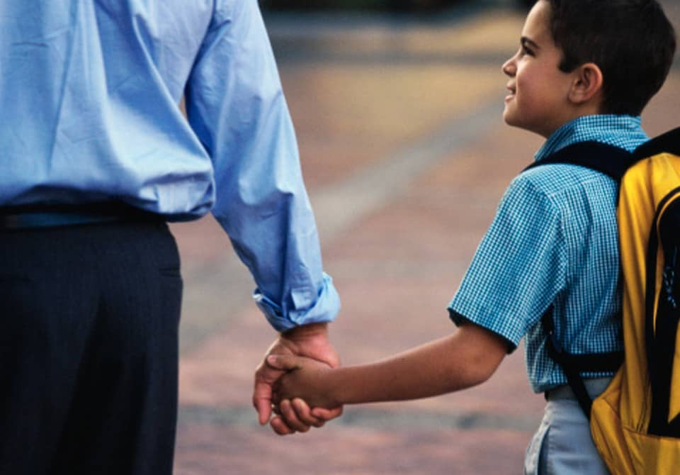 boy with backpack holding adult hand